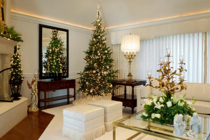 arbol navidad clásico para un salón grande de colores claros, adornos en dorado, pequeño árbol en la otra parte de la habitación