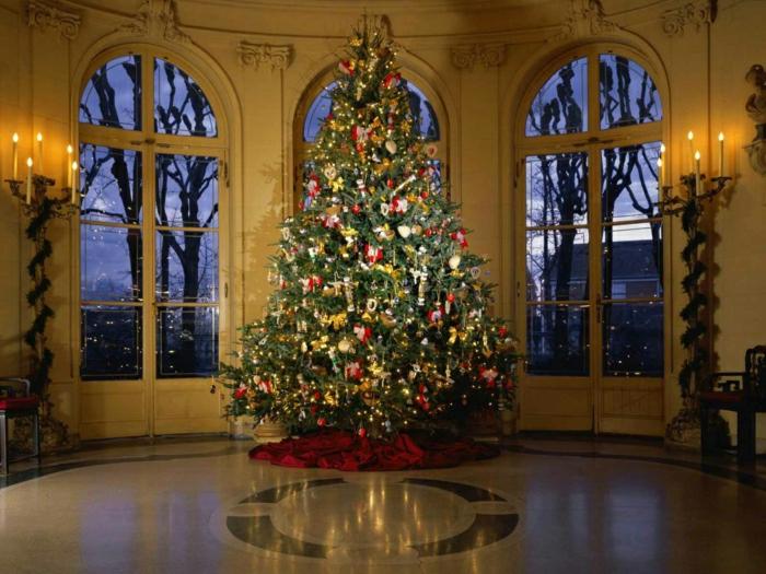 arboles de navidad originales, grande salón con ventanas de techo a suelo, árbol grande decorado con adornos rojos y color oro,