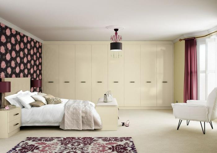 como decorar una habitacion, dormitorio beige con pared de acento en flores, lámpara de araña, sillón blanco, cortinas púrpuras