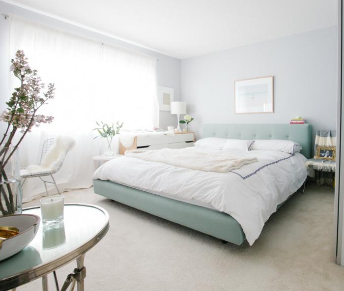 como decorar una habitacion, dormitorio con mucha luz, cama doble en azul celeste, mesa elíptica de vidrio, flores y planta verde