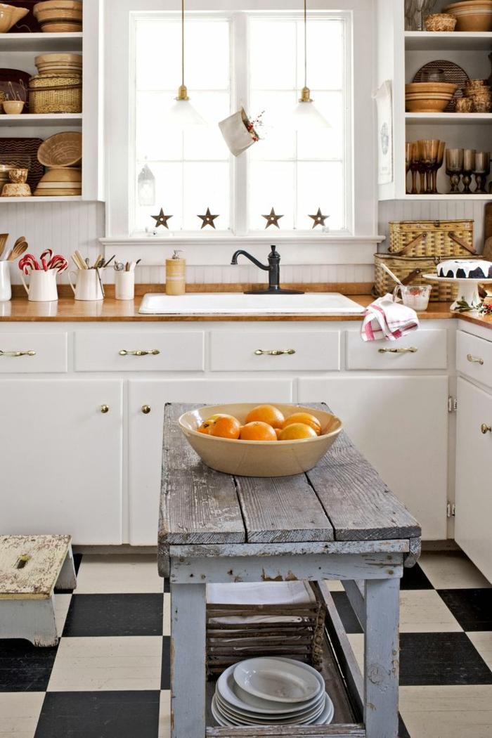 cocina comedor con mesa efecto desgastado, muchos armarios blancos, armario abiertos, utensilios de madera