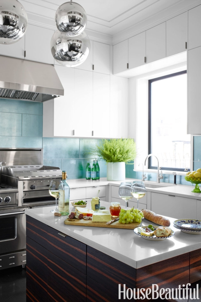 cocinas pequeñas alargadas en tonos frescos, con barra para comer, bolas metálicas para decorar, azulejos azules en la pared