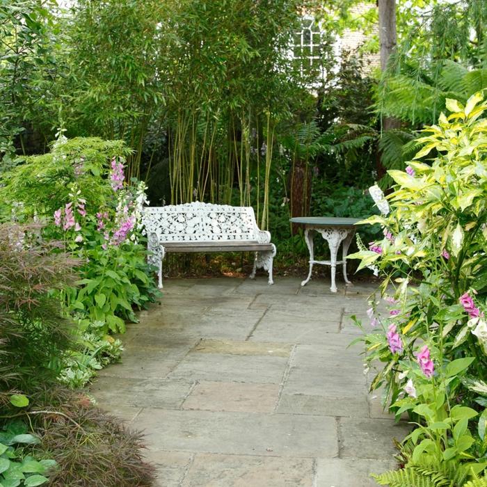 decoracion patios, bonito banco de madera, ornamentación que imita encaje, mesa redonda, arbustos grandes