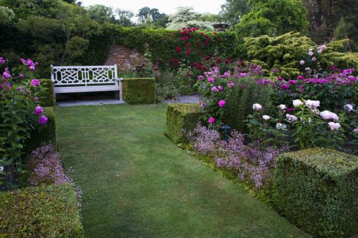 decoracion patios, césped rapada con arbustos de diseño, grande jardín con banco de madera blanco y muchas rosas