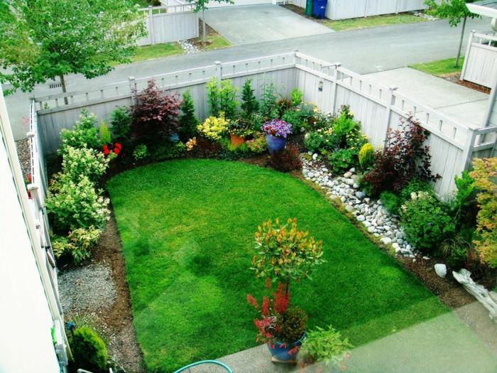 decoracion patios, espacio reducido, jardín pequeño con césped rapada y arbustos en los bordes, decoración de piedras de río