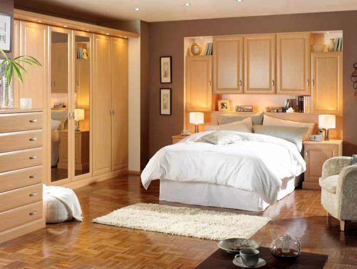 decoracion dormitorios, dormitorio de amdera clara, armario con paredes de espejo, cama doble con cabecero integradom sillón y tapete