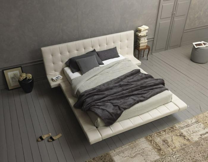 habitaciones de matrimonio, dormitorio en gris, suelo de tarima con alfombra, cama doble, cabecero tapizado, muchos libros