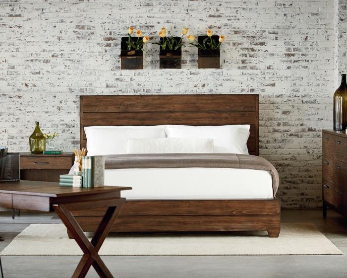 habitaciones de matrimonio, dormitorio con pared de ladrillo, cama de madera oscura, escritorio y decoración con tulipanes
