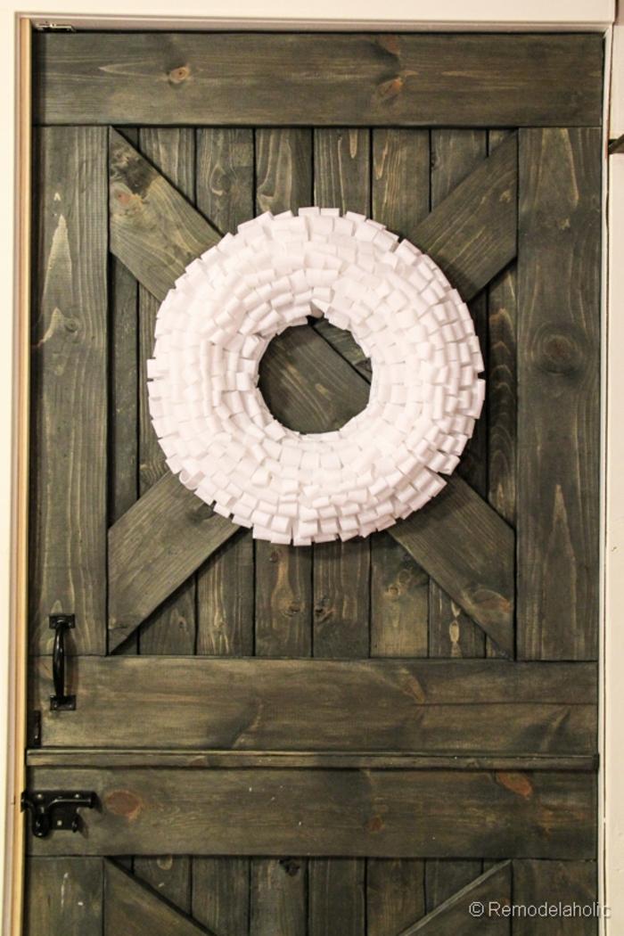 coronas de navidad, corona navideña de tela blanca hecha a mano sobre puerta de madera rústica