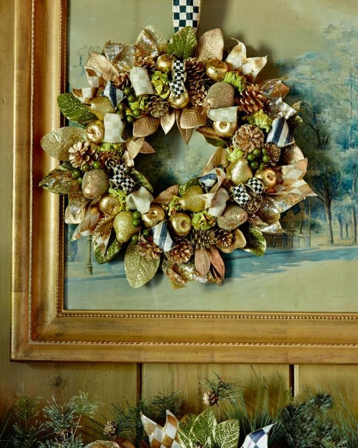 decoracion navideña casera, corona de navidad dorada con peras y manzanas artificiales, cuadro con marco de madera