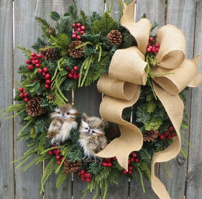 decoracion navideña casera, corona de navidad natural verde con muérdago, piñas y cinta, buhos pequeños peluches
