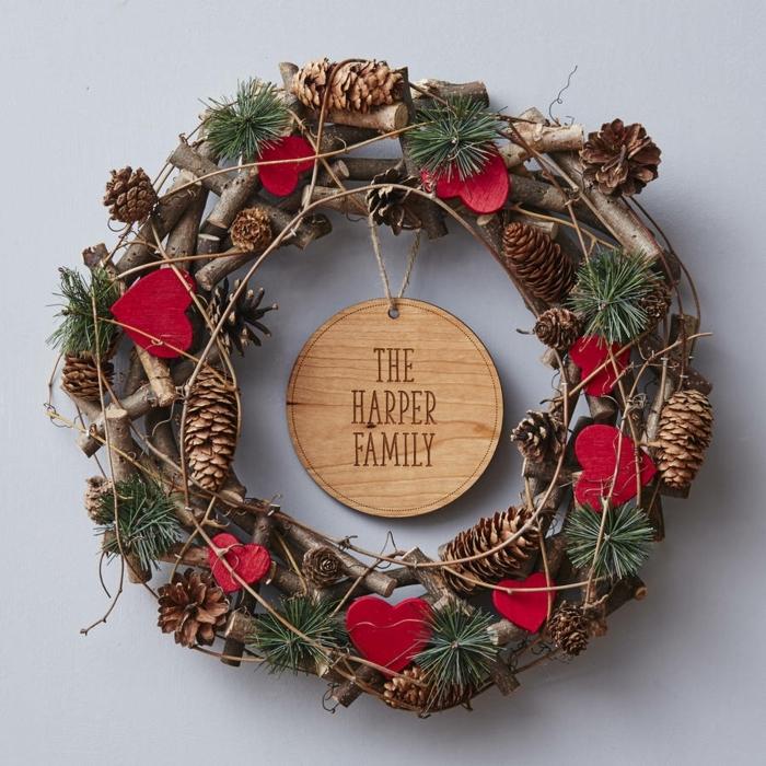 decoracion navideña casera, corona navideña natural de ramas, piñas y pino, corazones rojos, nombre de familia