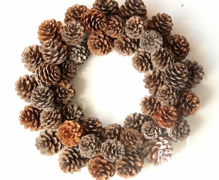 coronas de navidad, corona casera navideña hecha de piñas naturales pegadas sobre cuerda de metal