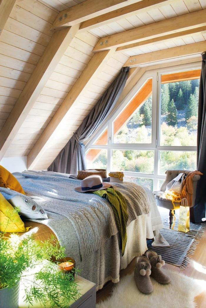 dormitorios modernos, cama doble en ático con techo de madera inclinado, mucha luz, planta verde