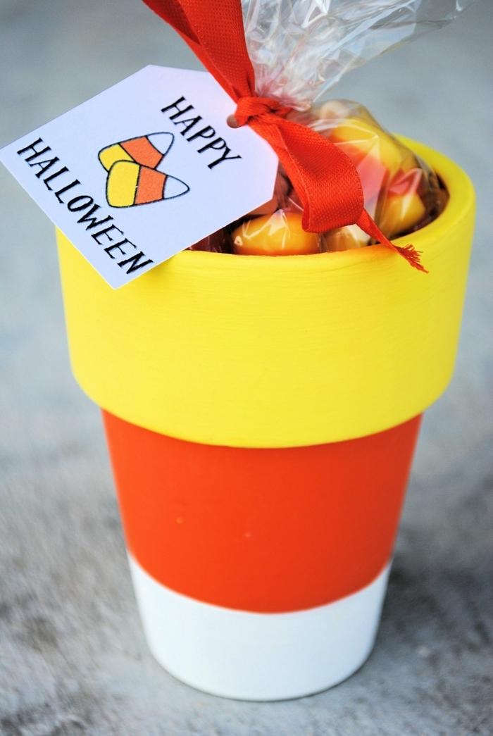 cosas de halloween, taza en blanco, naranja y amarillo llena de caramelos, decoración divertida y original