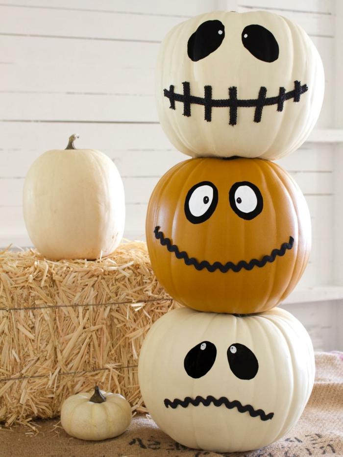 cosas de halloween, tres calabazas en blanco y beige con caras dibujas de zombies y decoración de hena