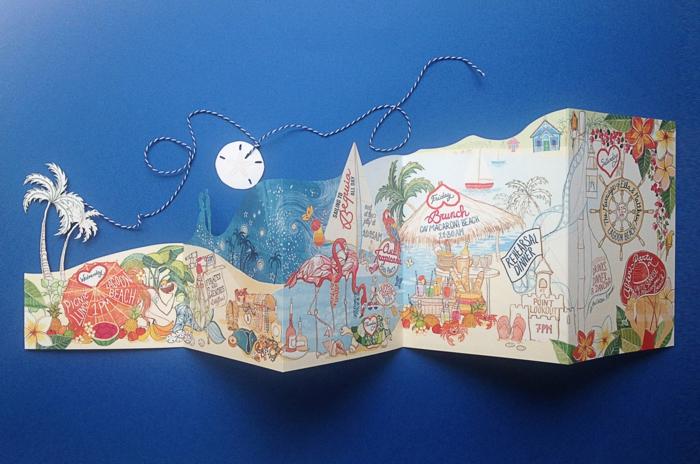 invitaciones de boda originales, invitación de boda plegable con dibujos de playa, sombrilla y flamencos sobre fondo azul