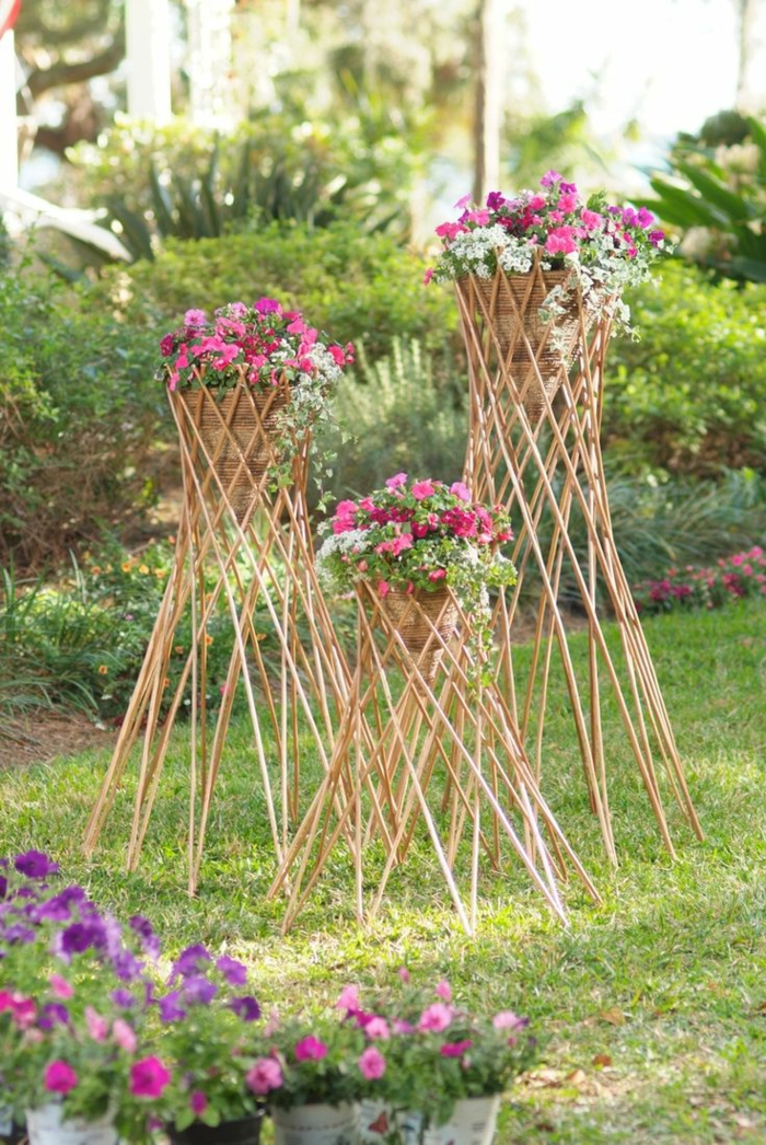 maceteros de madera, macetas tejidas elevadas en palos de madera, petunias rosa y blanco, jardín con césped
