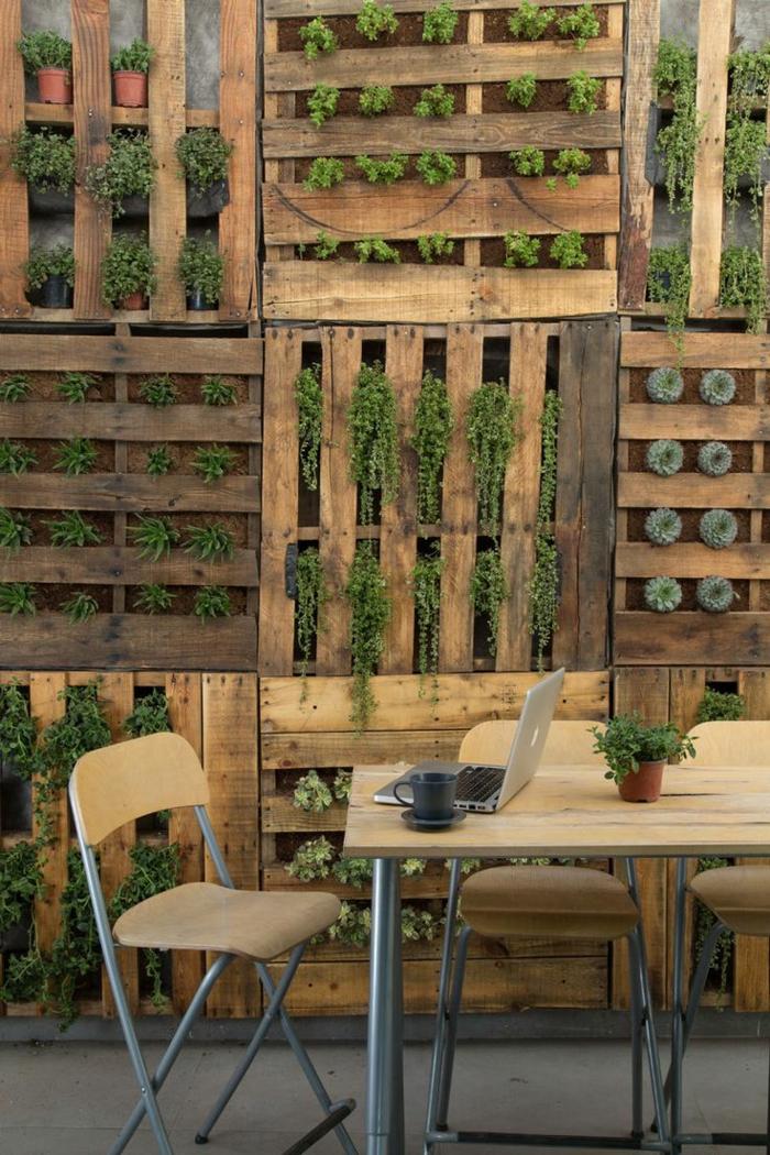 maceteros de madera, jardín vertical con palers, hierbas verdes y seimprevivas, mesa y silla de madera, computadora, taza de té