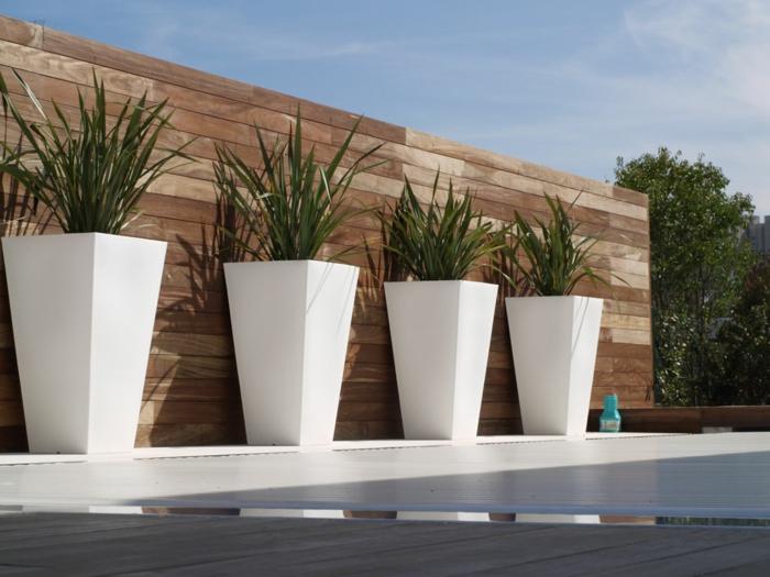 maceteros originales, decoración de patio con amceteros de hormigón blancos altos, plantas verdes, muro de tarima