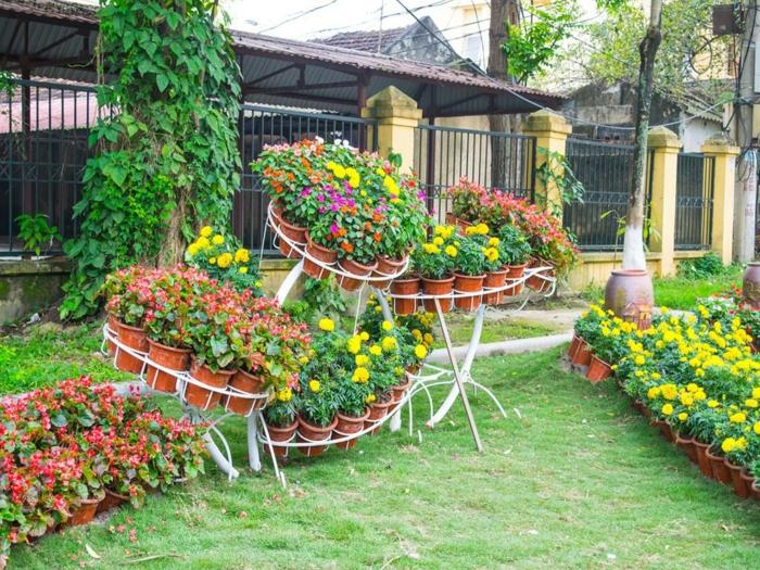 maceteros originales, jardín con césped, jardinera de alambre blanco con múltiples macetas pequeñas con flores