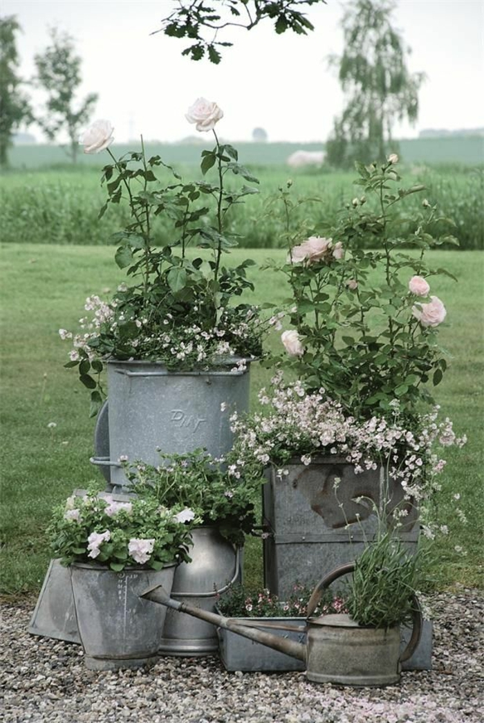 maceteros originales, decoración jardín romántico, macetas de contenedores de metal reciclados, rosas rosas, paisaje verde
