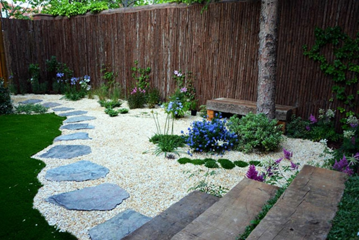 como hacer un jardin, pavimento de piedras pequeñas, sendero de piedras masivas, escaleras de madera, banco de madera simple, valla alta