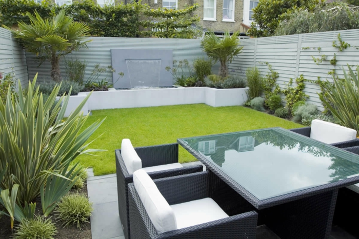 jardines con piedras, patio de estilo moderno y minimalista, muebles en tonos oscuros, césped rapada, palmeras pequeñas