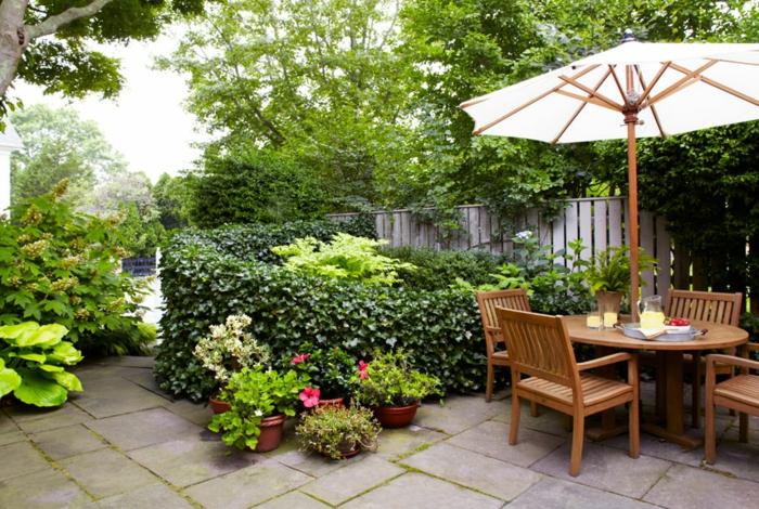 jardines con piedras, suelo empedrado, muebles y sombrilla de madera, arbustos enredadores, macetas con plantas pequeñas