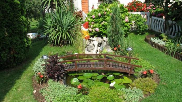 jardines con piedras, propuesta romántica para un patio pequeño, lago oval con lirios, fuente enano de madera