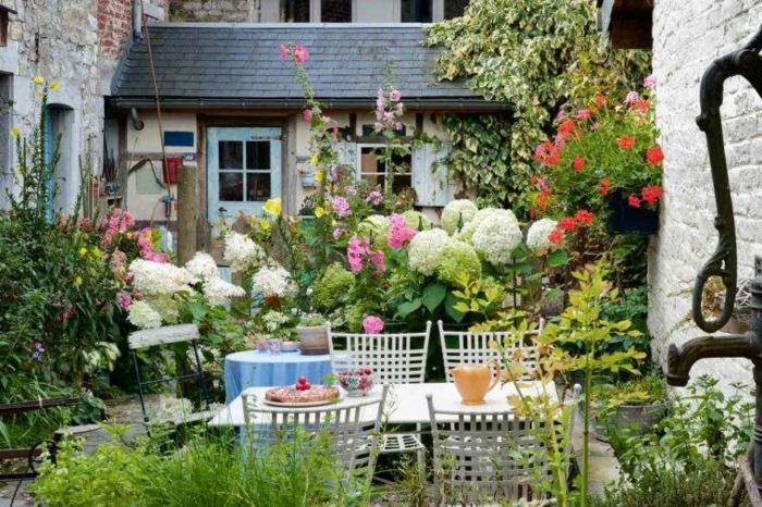 jardines con piedras, patio estilo provenzal colorido, con grandes flores, sillas y mesa de madera blancos, mucha decoración