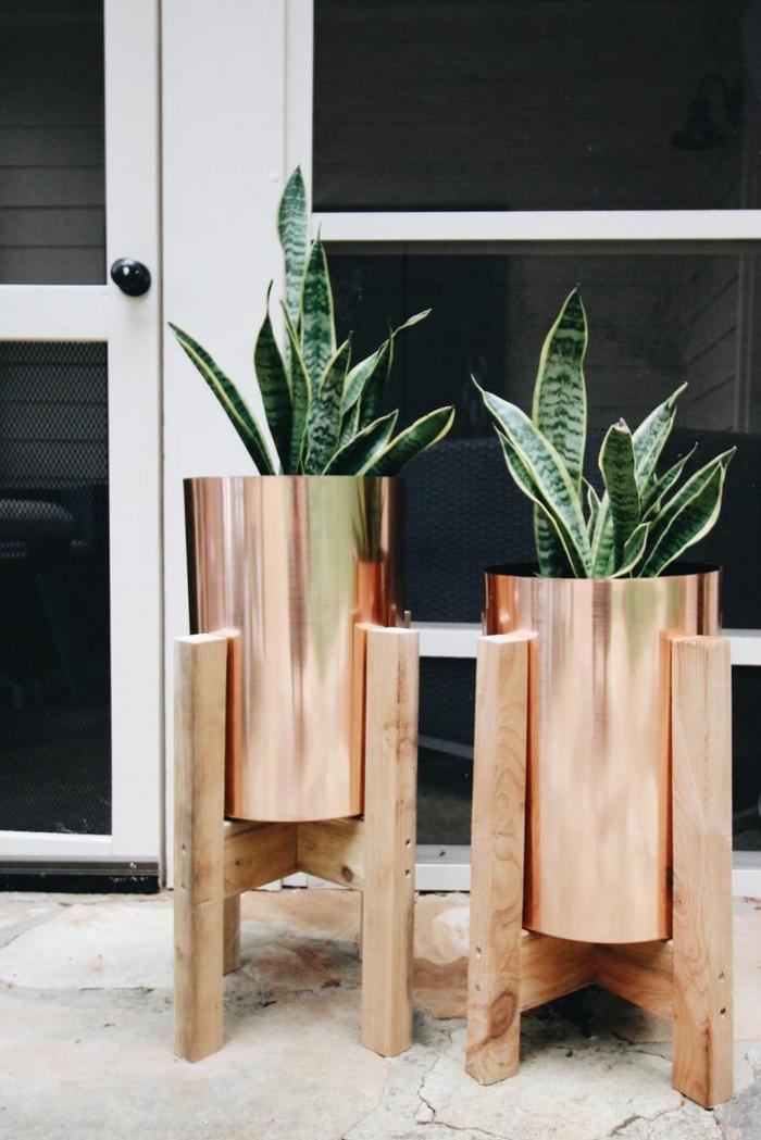 maceteros grandes, decoración de entrada con macetas de metal con piernas de madera, plantas verdes sin flor, puerta blanca