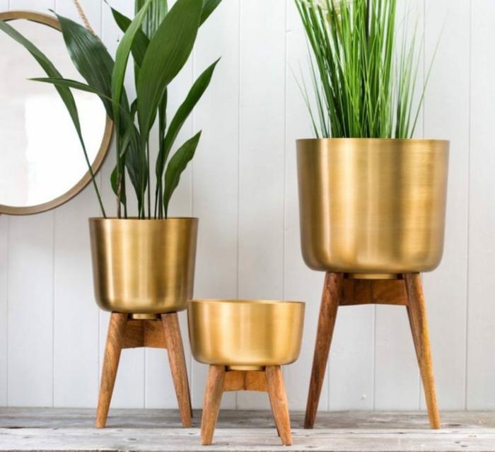 jardineras de madera, macetas modernas con piernas de madera y cuerpo de metal cobrizo, plantas verdes, pared con espejo