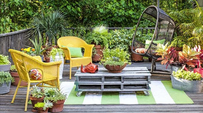 jardineras de madera, decoración de terraza con suelo de tarima, sillas de mimbre amarillo, mesa de palets, flores en macetas grandes
