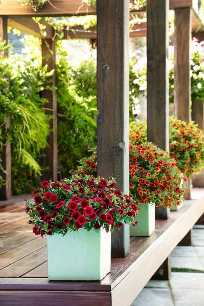 macetas grandes, plataforma de tarima con vigas, decoración con mecetas de cemento cuadradas con petunias rojas y naranjadas