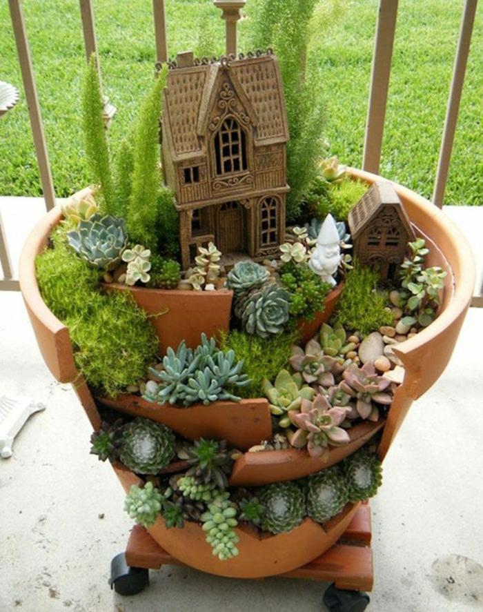 jardineras, decoración terraza, maceta de barro rota sobre ruedas decorada con castillo y siemprevivas
