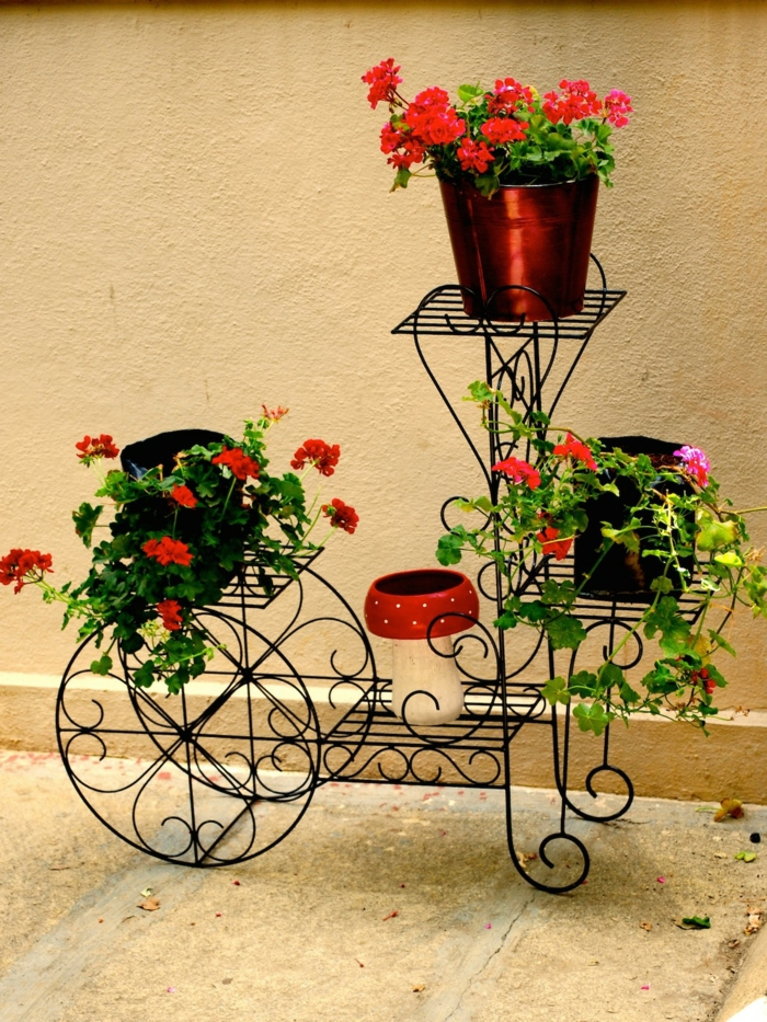 jardineras, macetero de alambres de metal en forma de bicicleta, macetas pequeñas con geranio rojo