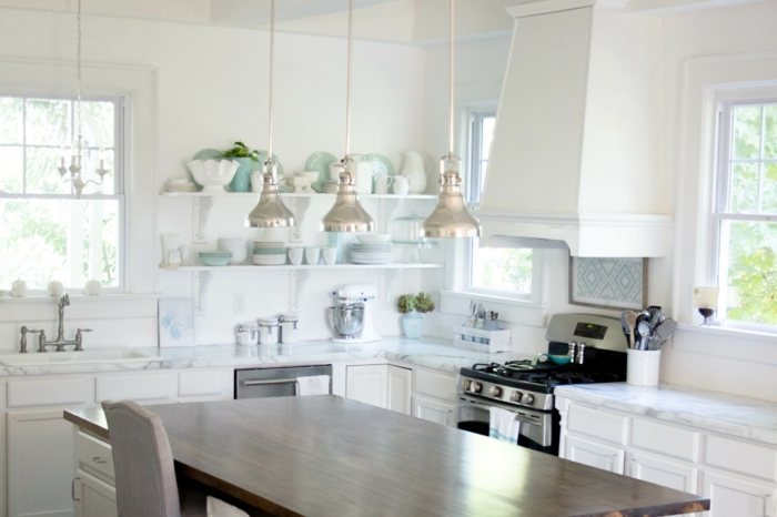 cocinas con isla, cocina pequeña con mesa rectangular de madera, lámparas de metal colgantes, estufas de gas, platos azules