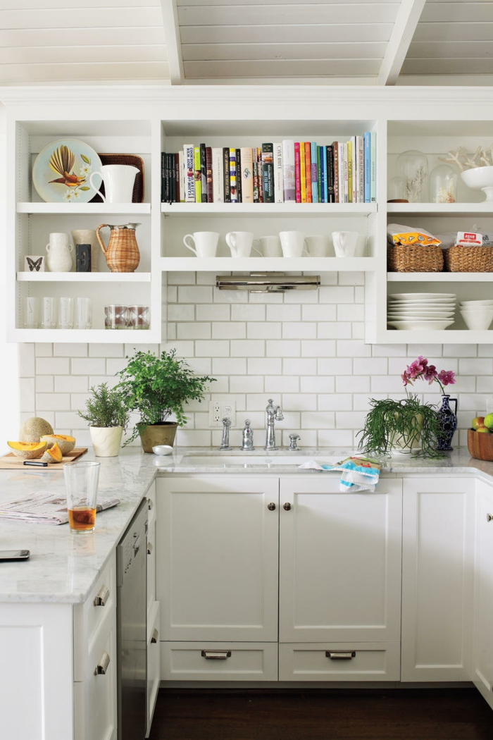 cocinas con isla, cocina pequeña blanca en forma U, encimera de mármol, estantes con tazas y libros, pared de ladrillo blanco, plantas verdes