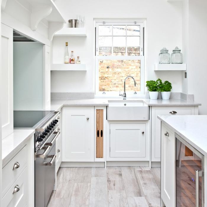 cocinas con isla, cocina blanca pequeña con isla, suelo de tarima, fregadero bajo ventana, plantas verdes