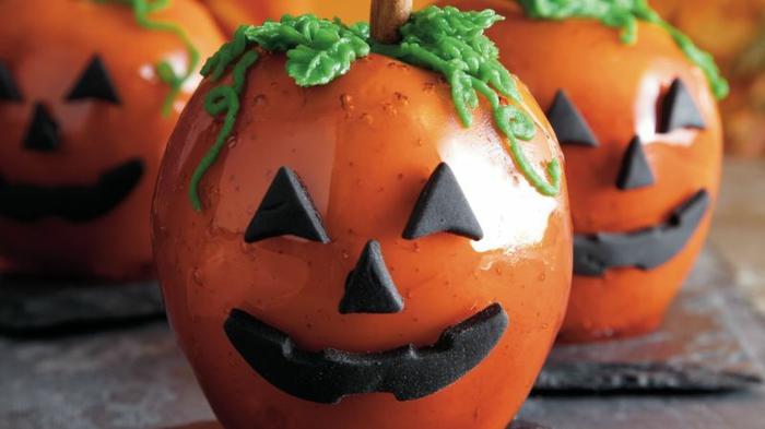 adornos halloween, manzanas acarameladas con jarabe de azúcar, decoradas como calabazas con caras