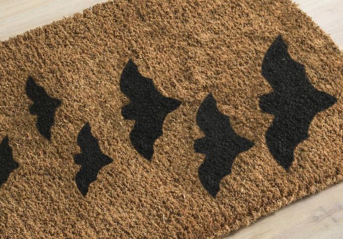 manualidades caseros, idea original, estampados en una estera beige, figuras de murciélagos negros, propuesta divertida para niños