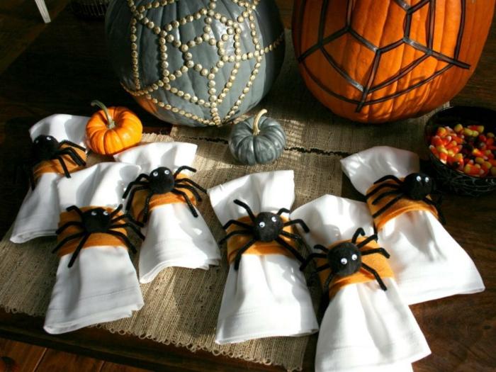 decoración halloween, servilletas decoradas con arañas, dos calabazas en naranja y verde con ornamentos