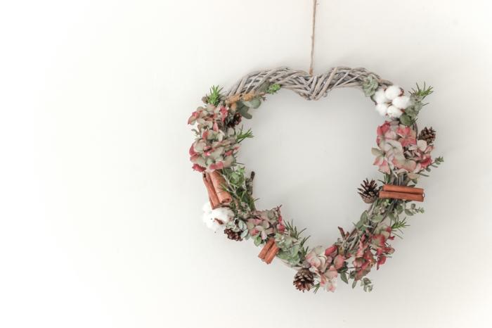 decoracion navideña manualidades, corona de navidad en forma de corazon, ramas secas, canela y piñas naturales, flores rosadas