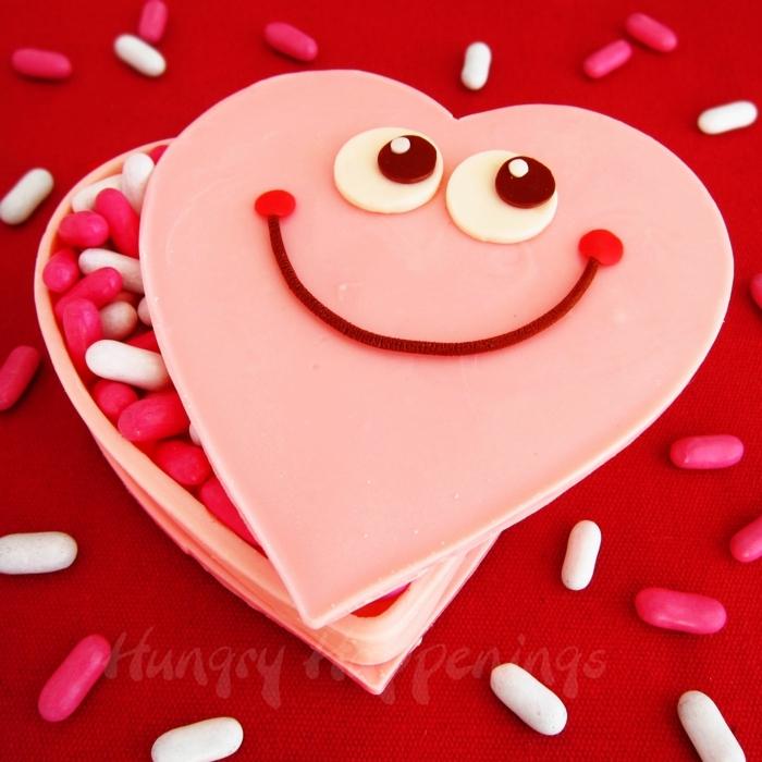 regalos san valentin, caja de chocolate rosado en forma de corazon con sonrisa lleno se caramelos en rosa y blanco