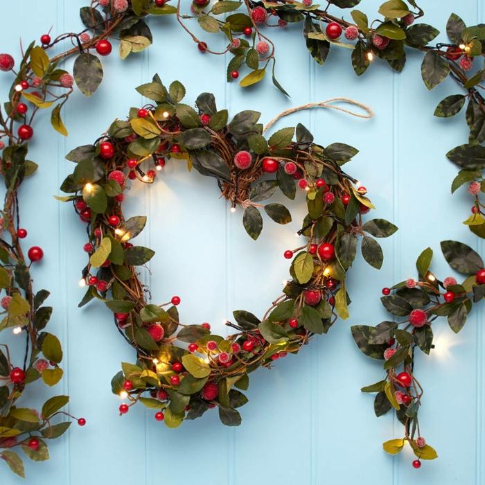 adornos de navidad caseros, corona de navidad con forma de corazon y guirnalda con hojas verdes, bayas rojas, luces navideñas