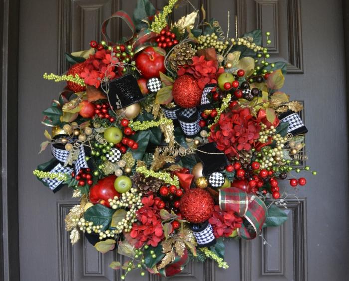 adornos de navidad caseros, corona de adviento con cintas decorativas. manzanas y ramas de muerdago artificiales
