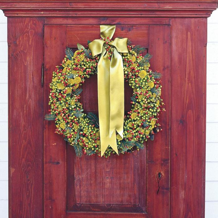 adornos de navidad caseros, corona de navidad en verde y amarillo, bayas y cinta dorada, armario de madera