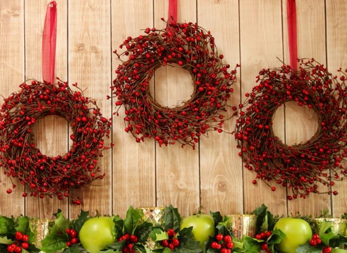 adornos de navidad caseros, tres coronas navideñas de muerdago rojo con cintas rojas, guirnalda con hojas verdes y manzanas
