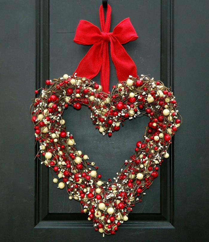 adornos de navidad caseros, corona navideña de muerdago blanco y rojo, forma de corazon, cinta roja